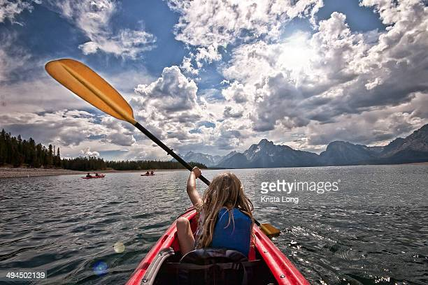 A girl kayaking on a summer day