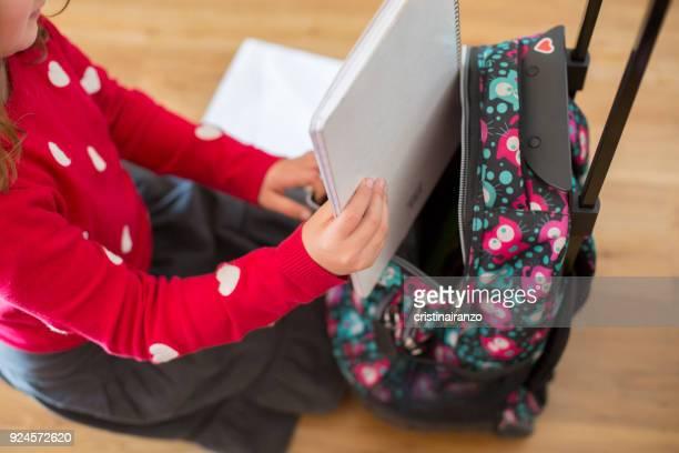 Girl keeping a notebook inside her backpack