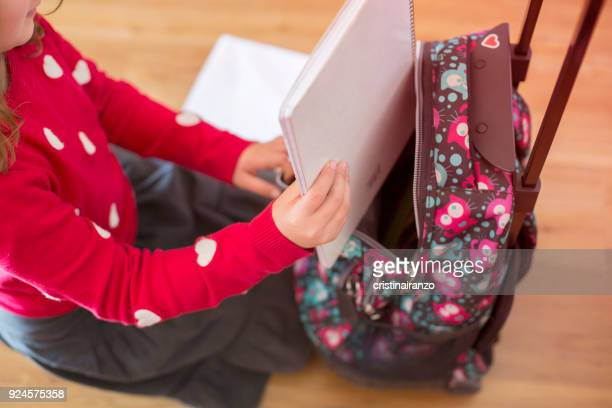 girl keeping a notebook inside her backpack - stipendium stock-fotos und bilder