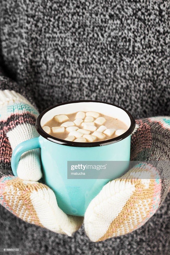 Girl keeps a mug of cocoa with marshmallows in mittens : Stock Photo