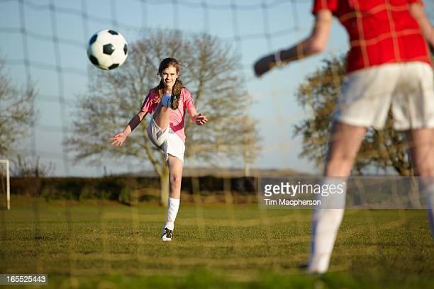 Girl kicking Football ball into goal