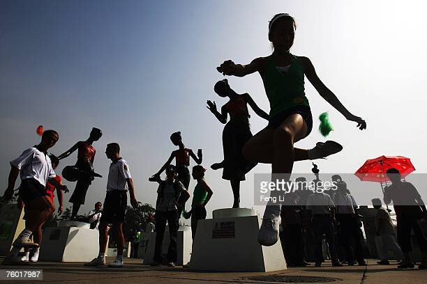 A girl kicks a shuttlecock beside a sculpture of shuttlecock kicking at the Hundreds of Millions of Masses Body building on August 8 2007 in Beijing...