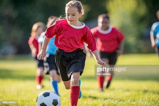 Girl Kicks Ball Up Field