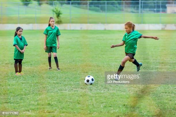 Girl kicks soccer ball during game