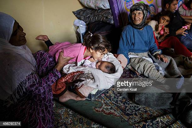 A girl kisses a baby sounded by her family in a temporary room in a refugee camp after crossing from Syria into Turkey in Suruc September 28 2014...