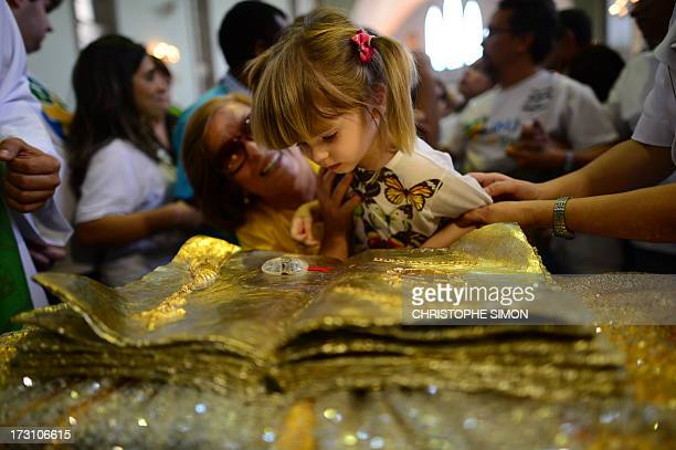 A girl kisses a relic during a mass officiated by Cardinal Stanislaw Rylko to celebrate the arrival in Brazil of the relics of blessed John Paul II...