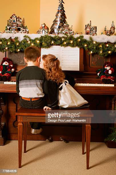Girl kisses boy playing piano