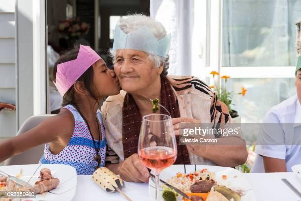Girl kisses grandma at outdoor Christmas lunch