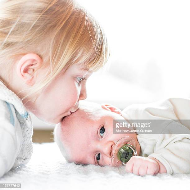 Girl kisses infant brother with white background
