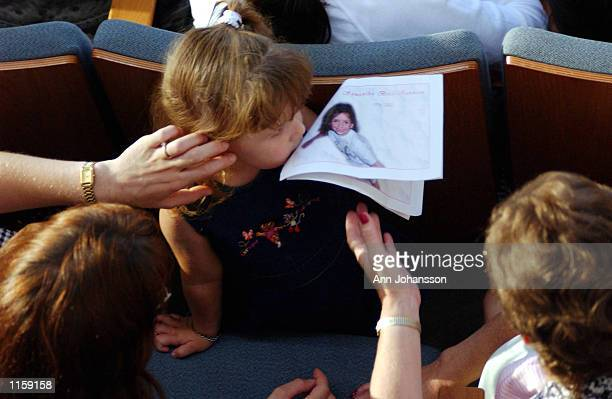 Girl kisses the picture of 5-year-old Samantha Runnion before Runnion's funeral at the Crystal Cathedral on July 24, 2002 in Garden Grove,...