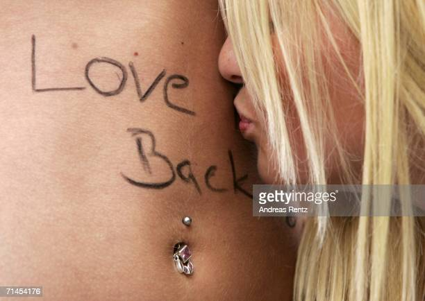A girl kisses the stomach of her girlfriend during the 16th annual Loveparade weekend July 15 2006 in Berlin Germany Over 300 DJs on 39 trucks so...