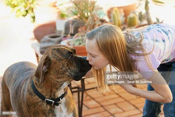 Girl (10-11) kissing boxer