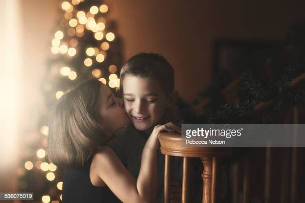 girl kissing boy's cheek at christmas - cheek stock pictures, royalty-free photos & images