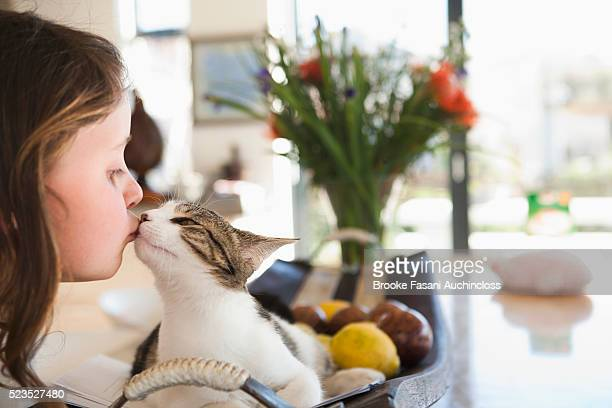 Girl (7-9) kissing cat