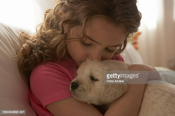 Girl (8-10) kissing dog