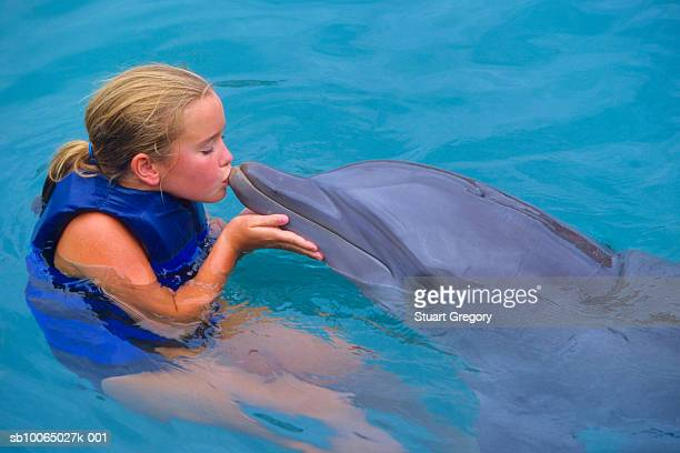 Girl (6-7) kissing dolphin in pool
