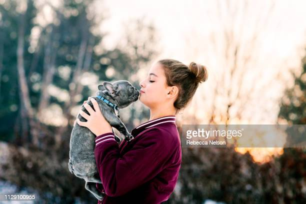 Girl kissing french bulldog puppy outdoors