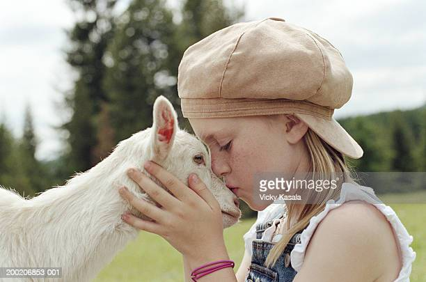 Girl (7-9) kissing goat on snout, side view