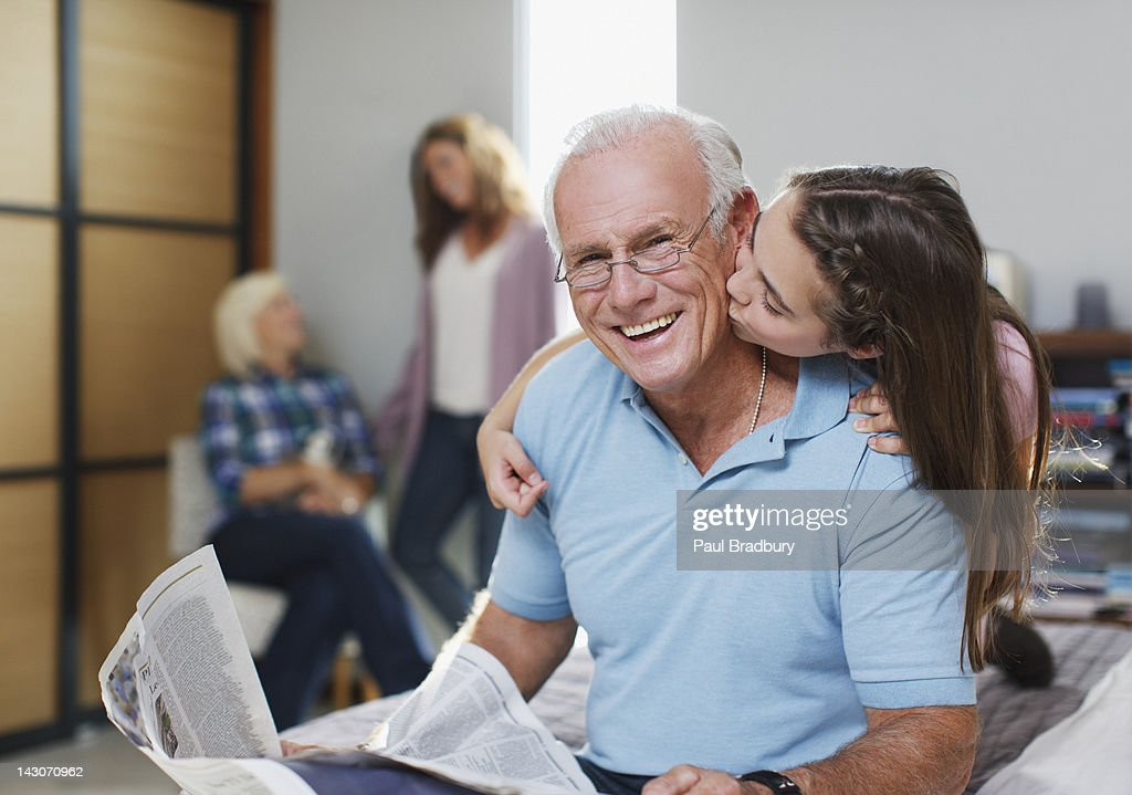 Girl kissing grandfather in home : Stock Photo