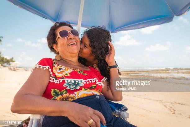 meisje zoenen oma en genieten van het tropische strand - latijns amerikaanse en hispanic etniciteiten stockfoto's en -beelden