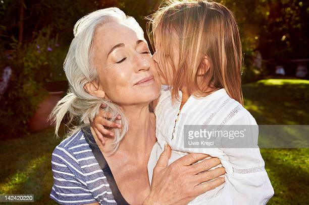 Girl (4-6) kissing grandmother on cheek, close-up