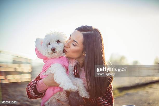 Girl kissing her dog poodle