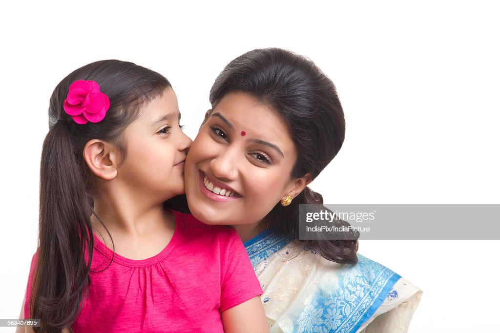Girl kissing her mother on the cheek : Stock Photo