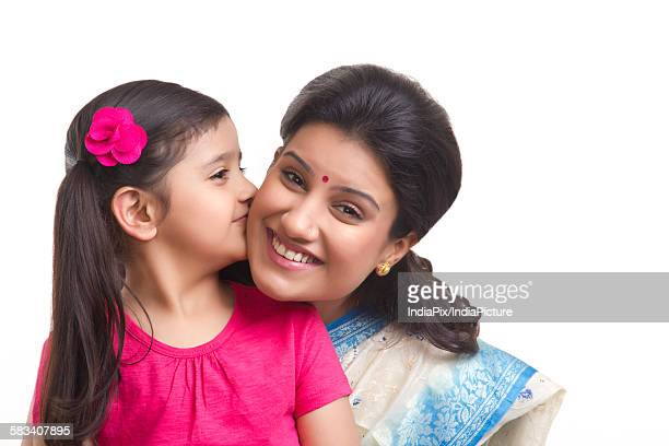 girl kissing her mother on the cheek - indian girl kissing stock photos and pictures
