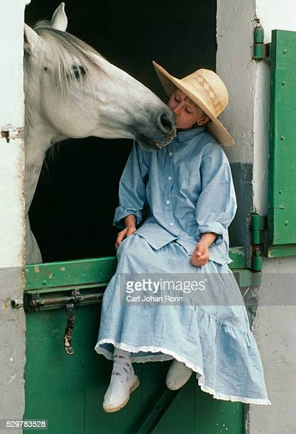 Girl kissing horse in stable