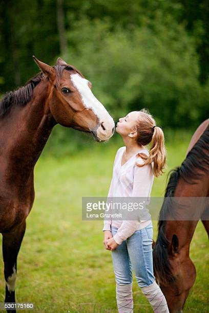 Girl kissing horse on meadow