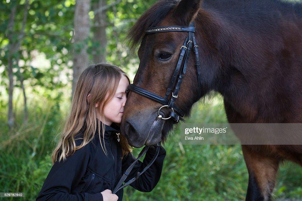 Girl kissing horse : Stock Photo