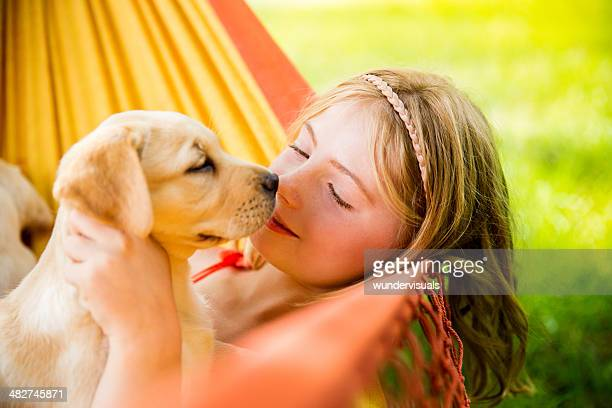 Girl kissing labrador puppy