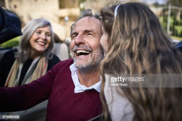 girl kissing laughing grandfather in convertible car - prosperity stock pictures, royalty-free photos & images