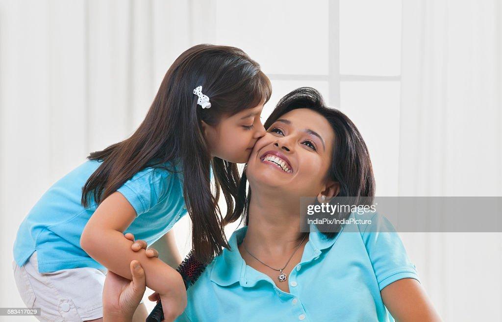 Girl kissing mother on cheek : Stock Photo