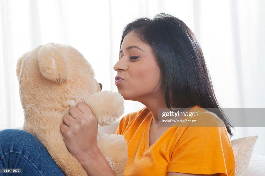 Girl kissing teddy bear : Stock Photo