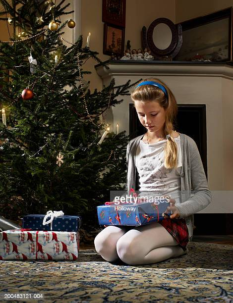 Girl (9-11) kneeling beside Christmas tree looking at present