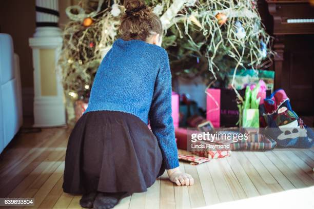 A girl kneeling in front of wrapped gifts under a Christmas tree