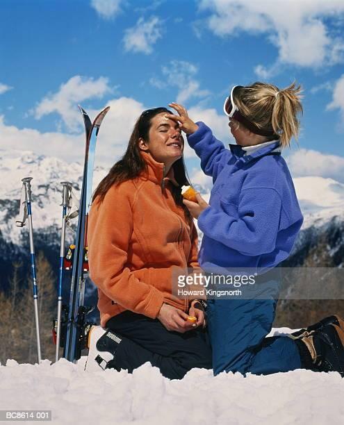 Girl (10-12) kneeling in snow, applying suncream to woman's face