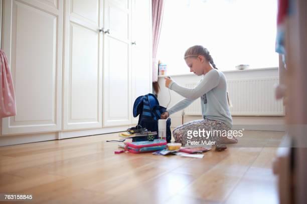 Girl kneeling on floor packing school bag