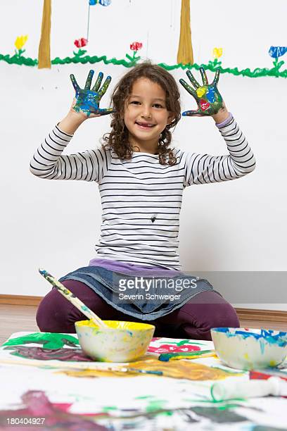 Girl kneeling on floor with painted hands