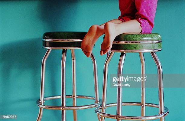 Girl (6-8) kneeling on stool, low section