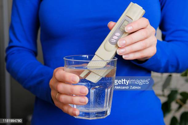 girl lab technician holding a digital tester to determine water quality control and lowers it into a glass of drinking water for analysis, at home, close-up. - alkaline stock pictures, royalty-free photos & images