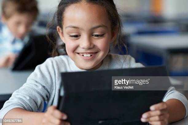 Girl laughing and working on tablet in classroom
