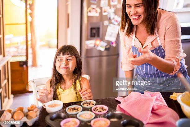 Girl laughing because her mom put dough on her nose
