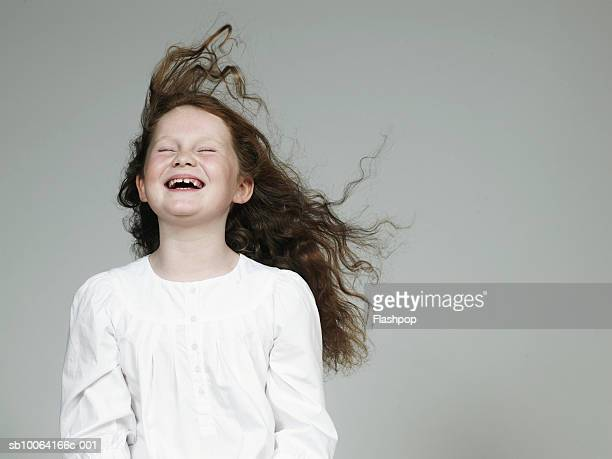 Girl (8-9) laughing, eyes closed, close-up