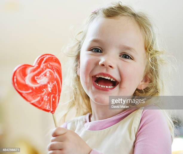 Girl laughing holding a heart shaped lollipop