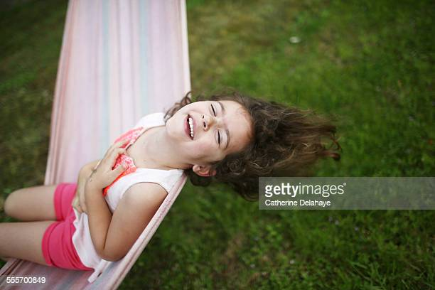 a girl laughing on a hammock - delahaye stock photos and pictures