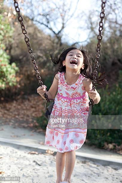 Girl laughing on swing