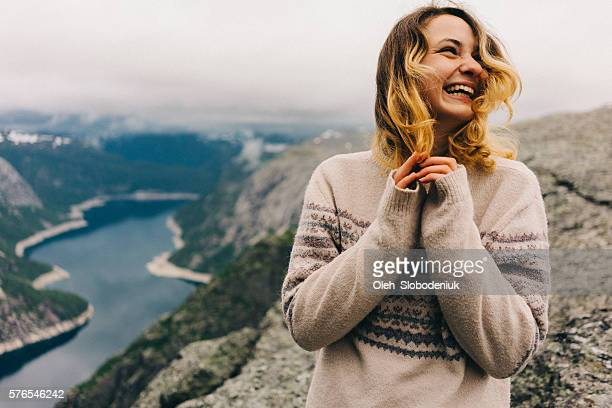 girl laughing on the trolltunga - nordic countries stock pictures, royalty-free photos & images