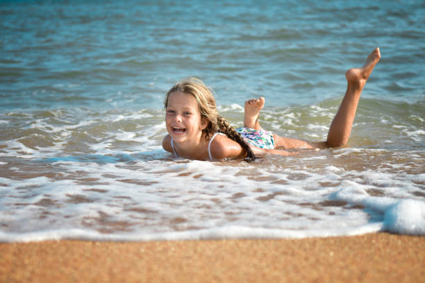 Girl laughing while swimming in the waves on the beach